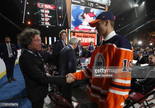 Philip Broberg eighth overall pick of the Edmonton Oilers shakes the hand of team owner Daryl Katz on the draft floor during the first round of the...