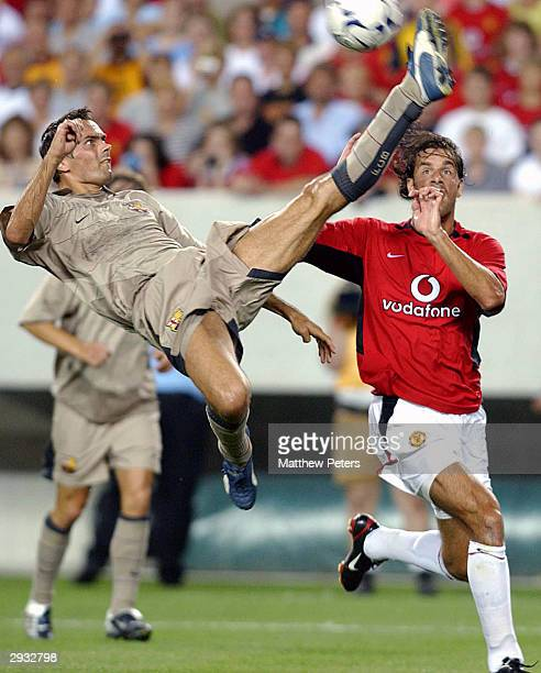 Philip Cocu takes to the air to clear the ball from Ruud Van Nistelrooy during the friendly match between Manchester United v Juventus in Giants...