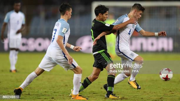 Philip Foden and George McEachran of England battle for the ball with Diego Lainez of Mexico during the FIFA U17 World Cup India 2017 group F match...