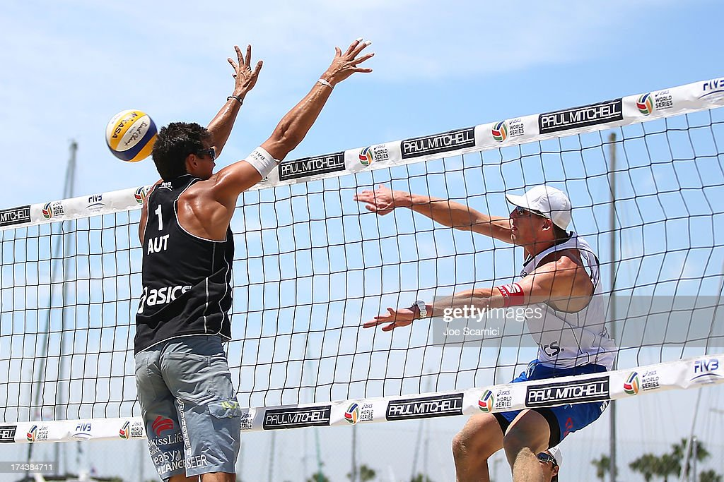 Philip Gabathuler of Switzerland (R) spikes the ball past Peter Eglseer of Austria during the round of pool play at the ASICS World Series of Beach Volleyball - Day 3 on July 24, 2013 in Long Beach, California.