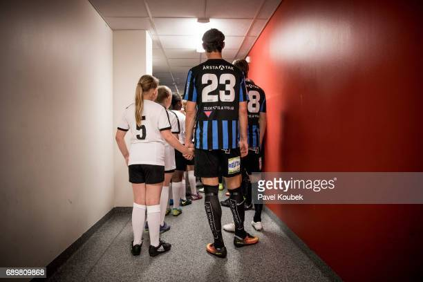 Philip Haglund of IK Sirius FK holds the hand of a junior player as they are getting ready to enter the pitch during the Allsvenskan match Between...