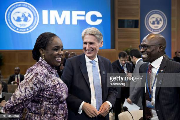 Philip Hammond UK chancellor of the exchequer center and Malusi Gigaba South Africa's finance minister right speak with an attendee during an...