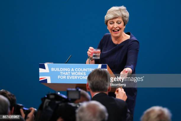 Philip Hammond UK chancellor of the exchequer hands Theresa May UK prime minister and leader of the Conservative Party a cough sweet as she delivers...