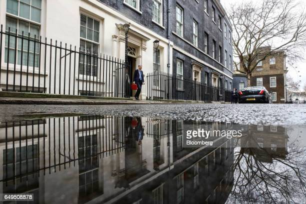 Philip Hammond UK chancellor of the exchequer holds the dispatch box containing the budget as he exits 11 Downing Street on his way to present his...