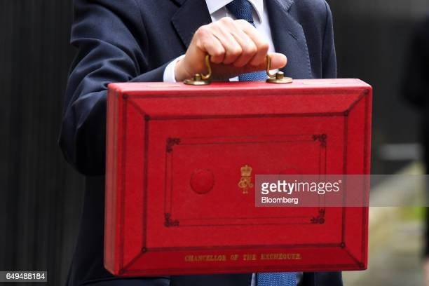 Philip Hammond UK chancellor of the exchequer poses with the dispatch box containing the budget as he exits 11 Downing Street on his way to present...
