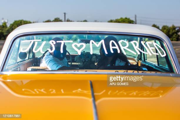 TOPSHOT Philip Hernandez and Marcela Peru pose for a picture inside their car at the Honda Center parking lot after they were married by a county...