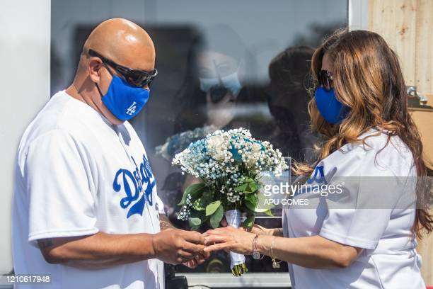 TOPSHOT Philip Hernandez puts the ring on his bride Marcela Peru as Clerk Recorder Erika Patronas looks on during their wedding ceremony on April 21...
