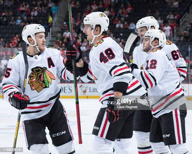Philip Holm of the Chicago Blackhawks celebrates his second period goal with teammates Alex DeBrincat Slater Koekkoek and Andrew Shaw during a...