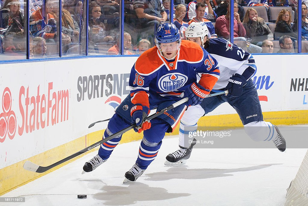 Philip Larsen #36 of the Edmonton Oilers skates with the puck while Chris Thorburn #22 of the Winnipeg Jets chases him during a preseason NHL game at Rexall Place on September 23, 2013 in Edmonton, Alberta, Canada.