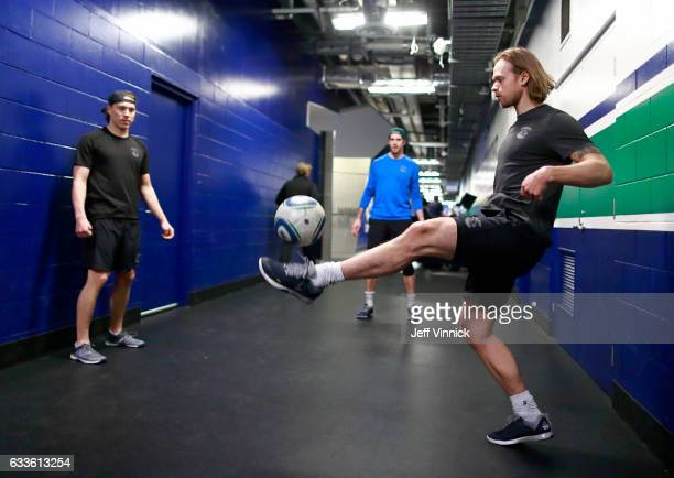 Philip Larsen of the Vancouver Canucks kicks the soccer ball as he warms with teammates Jacob Markstrom and Markus Granlund before their NHL game...