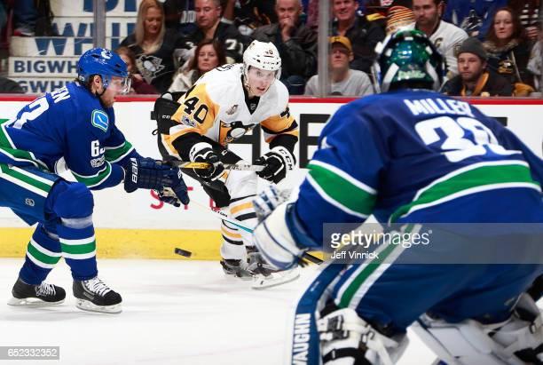 Philip Larsen of the Vancouver Canucks looks on as Oskar Sundqvist of the Pittsburgh Penguins takes a shot against Ryan Miller during their NHL game...