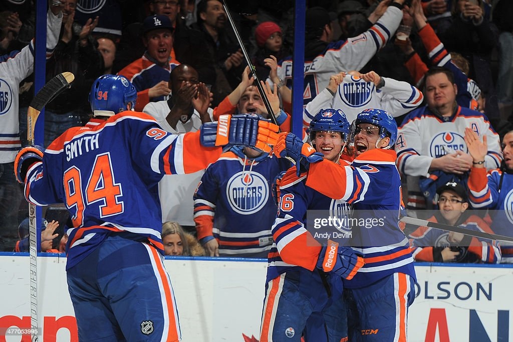 Philip Larson #46, David Perron #57 and Ryan Smyth #94 of the Edmonton Oilers celebrate after a goal in a game against the New York Islanders on March 6, 2014 at Rexall Place in Edmonton, Alberta, Canada.