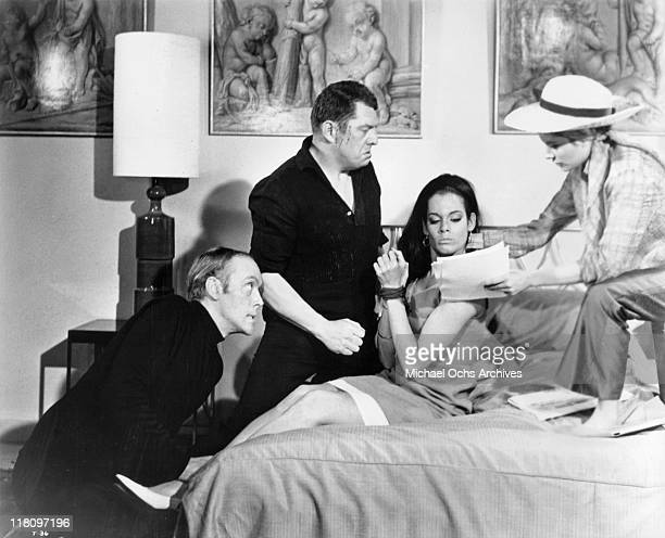 Philip Locke and Michael Brennan tie up Martine Beswick while Luciana Paluzzi shows her papers to read in a scene from the film 'Thunderball' 1965