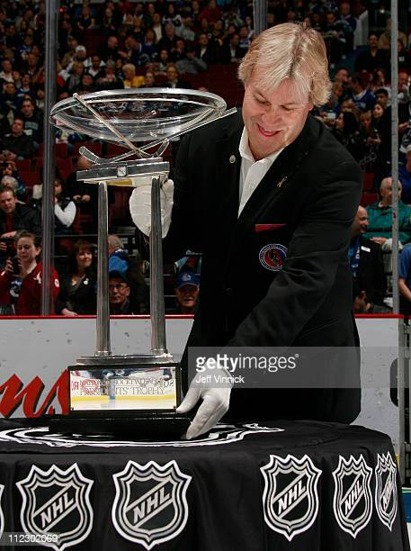 Philip Pritchard Vice President of Hockey Operations at the Hockey Hall of Fame places the Presidents' trophy on a table during the game between the...