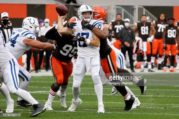 Philip Rivers of the Indianapolis Colts throws a pass while being hit by Olivier Vernon of the Cleveland Browns in the second quarter at FirstEnergy...