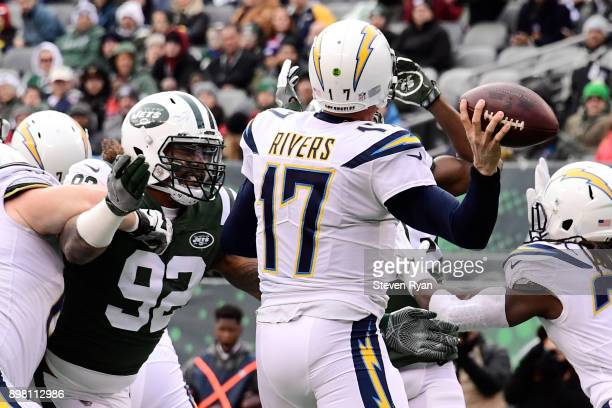 Philip Rivers of the Los Angeles Chargers attempts a pass under pressure from Leonard Williams of the New York Jets during the first half of an NFL...