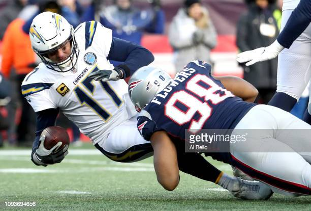 Philip Rivers of the Los Angeles Chargers is tackled by Trey Flowers of the New England Patriots during the third quarter in the AFC Divisional...