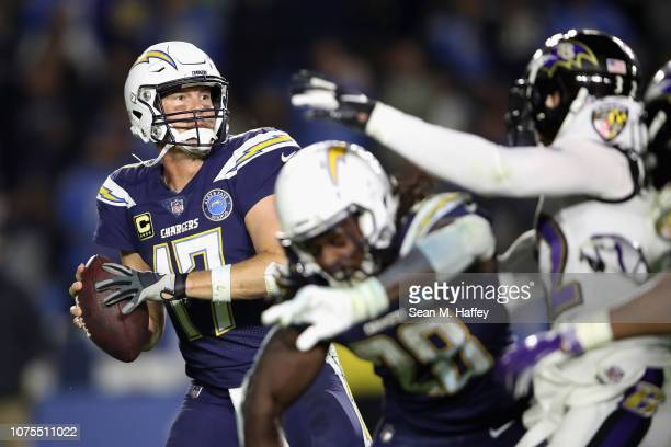 Philip Rivers of the Los Angeles Chargers passes the ball under pressure in the pocket during the second half of a game against the Baltimore Ravens...