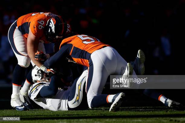 Philip Rivers of the San Diego Chargers gets sacked by Jeremy Mincey and Mitch Unrein of the Denver Broncos in the first quarter during the AFC...