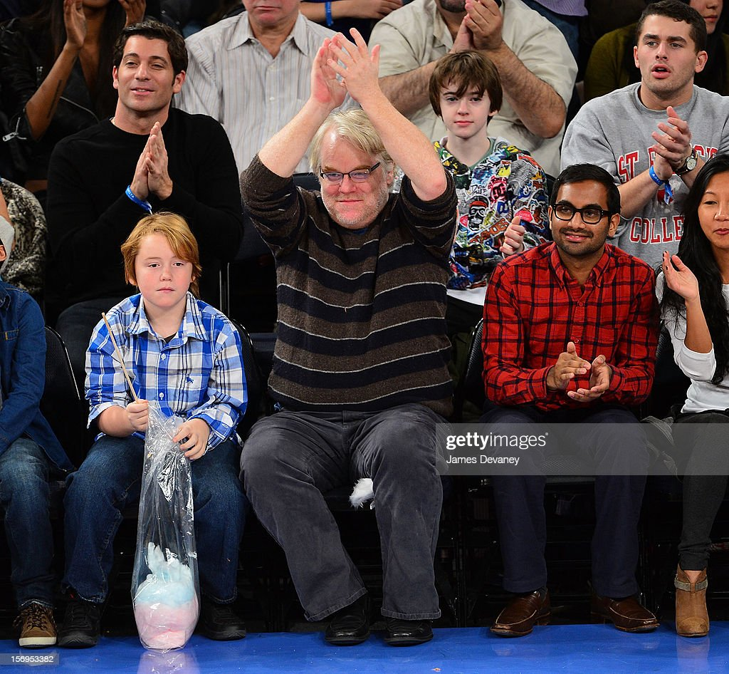 Philip Seymour Hoffman (C), Cooper Alexander Hoffman (L) and Aziz Ansari attend the Detroit Pistons vs New York Knicks game at Madison Square Garden on November 25, 2012 in New York City.