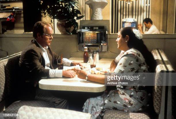 Philip Seymour Hoffman sits in a restaurant with Camryn Manheim in a scene from the film 'Happiness', 1998.