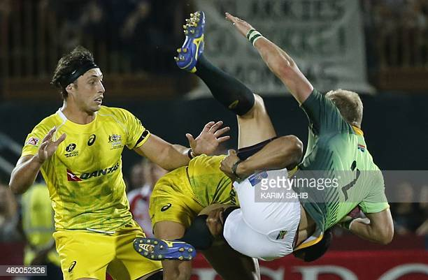 Philip Snyman of South Africa is tackled by Pama Fou and Sam Myers of Australia during their final rugby match of the Dubai leg of IRB's Sevens World...