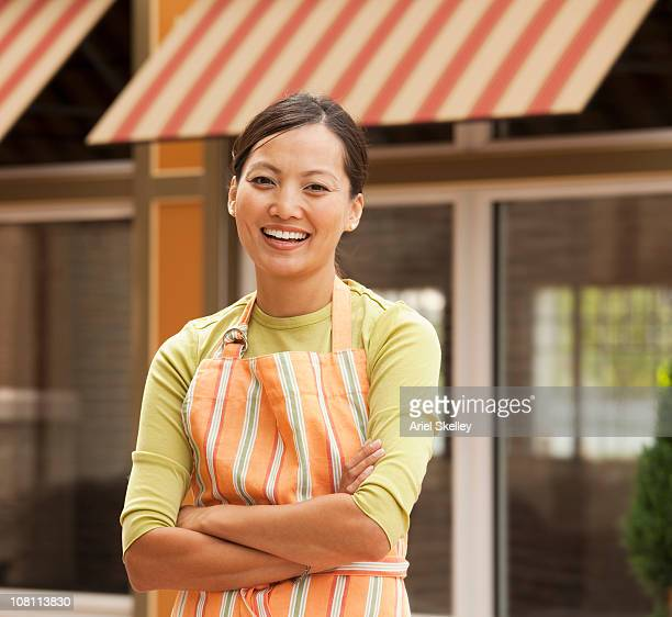philipino woman in apron with arms crossed outside of shop - philippine independence day stock pictures, royalty-free photos & images