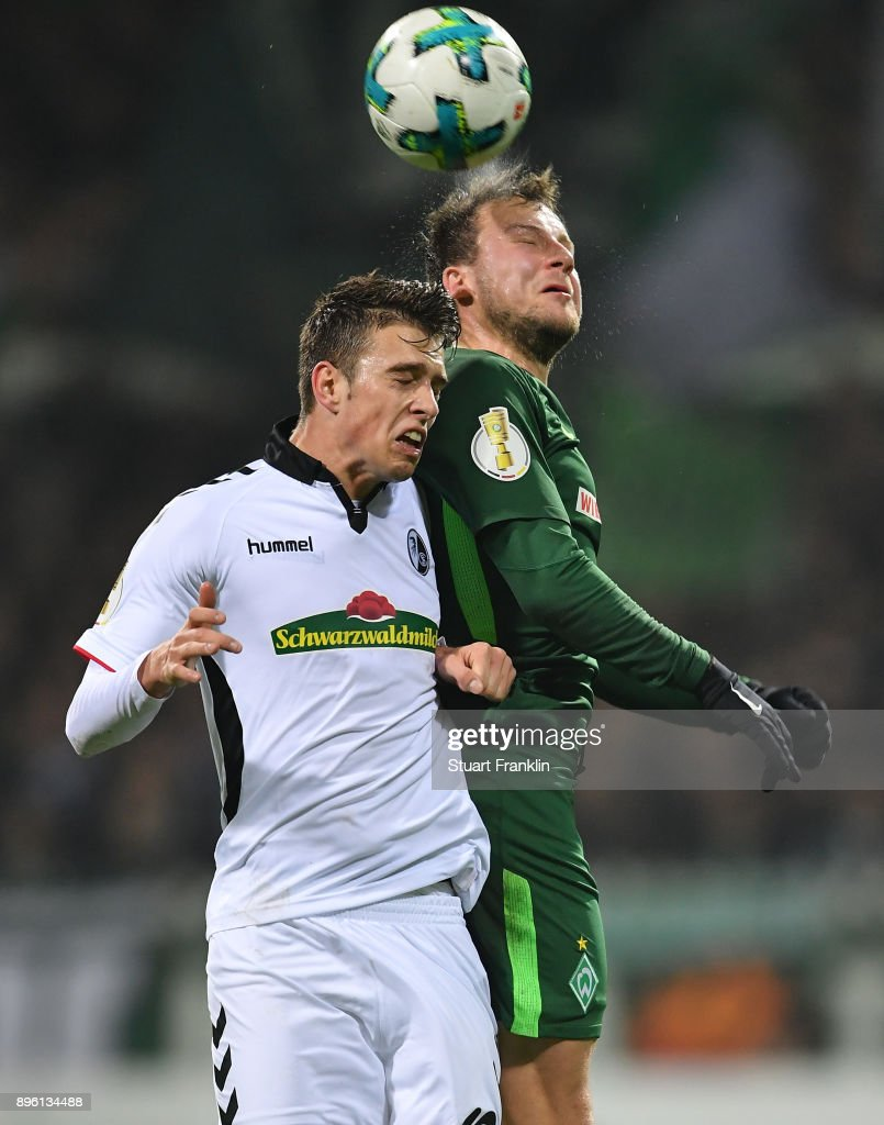 Philipp Bargfrede of Bremen is challenged by Janik Haberer of Freiburg during the DFB Cup match between Werder Bremen and SC Freiburg at Weserstadion on December 20, 2017 in Bremen, Germany.