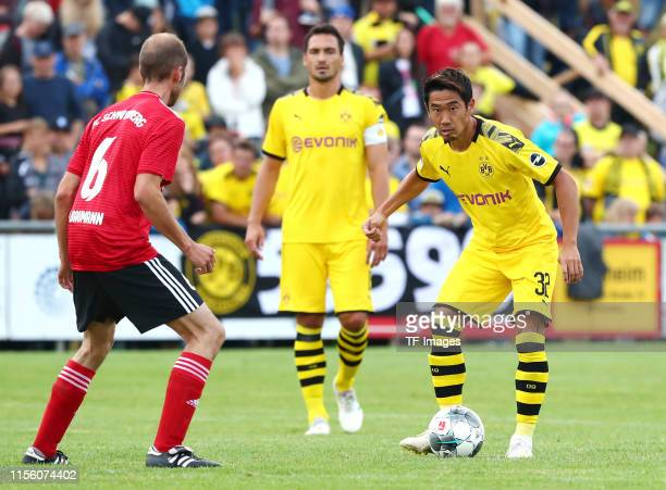 Philipp Baumann of FC Schweinberg and Shinji Kagawa of Borussia Dortmund battle for the ball during the preseason friendly match between FC...