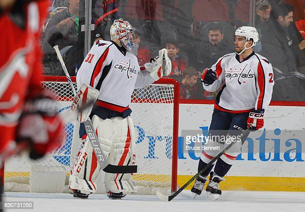 Philipp Grubauer and Matt Niskanen of the Washington Capitals celebrate their 62 victory over the New Jersey Devils at the Prudential Center on...