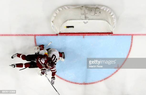 Philipp Grubauer of Germany collides with Miks Indrasis of Latvia during the 2017 IIHF Ice Hockey World Championship game between Germany and Latvia...