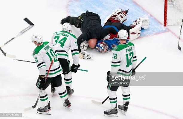 Philipp Grubauer of the Colorado Avalanche is attended to by a trainer following a second period injury against the Dallas Stars in Game One of the...