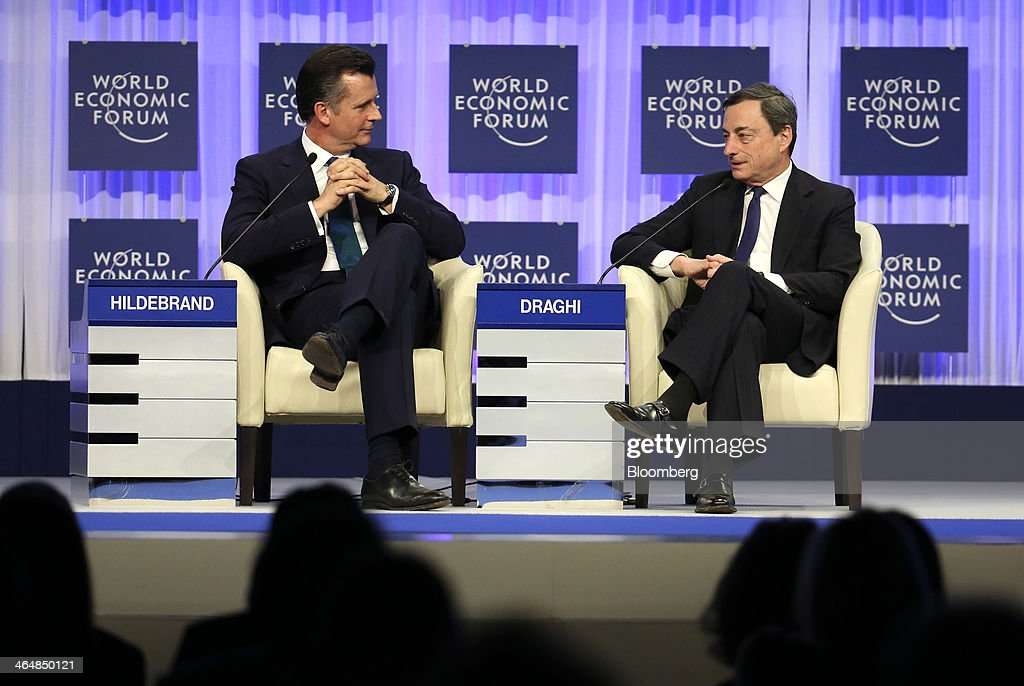 Philipp Hildebrand, vice chairman of Blackrock Intl. Ltd., left, listens as Mario Draghi, president of the European Central Bank (ECB), speaks during a session on day three of the World Economic Forum (WEF) in Davos, Switzerland, on Friday, Jan. 24, 2014. World leaders, influential executives, bankers and policy makers attend the 44th annual meeting of the World Economic Forum in Davos, the five day event runs from Jan. 22-25. Photographer: Chris Ratcliffe/Bloomberg via Getty Images