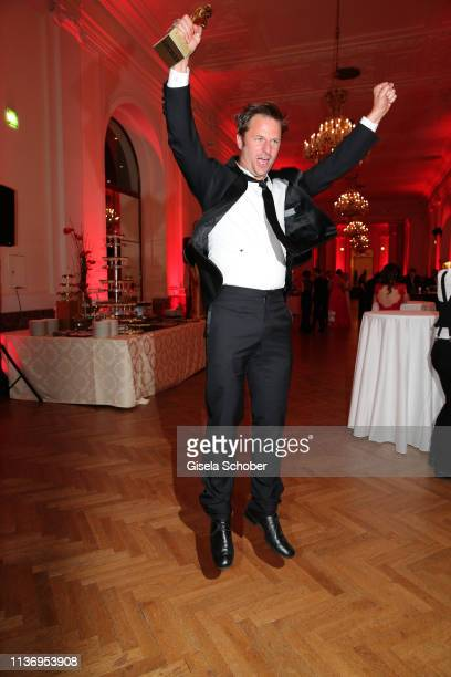 Philipp Hochmair poses with his award for most popular actor, jumps during the ROMY award at Hofburg Vienna on April 13, 2019 in Vienna, Austria.