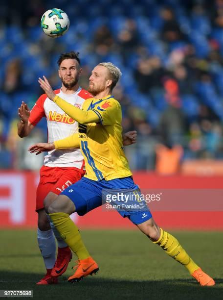 Philipp Hofmann of Braunschweig is challenged by Benedikt Gimber of Regensburg during the Second Bundesliga match between Eintracht Braunschweig and...