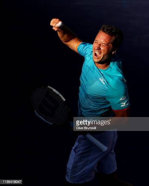 Philipp Kohlschreiber of Germany leaps into the air to celebrate after his straight sets victory against Novak Djokovic of Serbia during their men's...