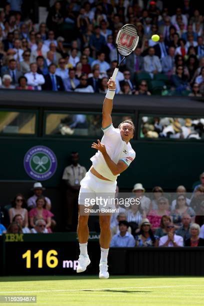 Philipp Kohlschreiber of Germany serves in his Men's Singles first round match against Novak Djokovic of Serbia during Day one of The Championships -...