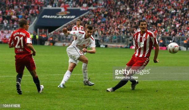 Philipp Lahm and Daniel van Buyten of Muenchen watch Adam Szalai of Mainz scoring his first goal of Mainz during the Bundesliga first league match...