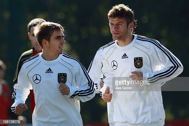 Philipp Lahm and Thomas Mueller chat as they warm up during a training session of the German national football team on the artificial turf of the...