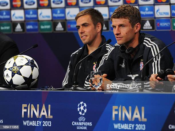 Philipp Lahm and Thomas Mueller look on during a FC Bayern Muenchen press conference ahead of the UEFA Champions League final match against Borussia...