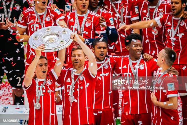 Philipp Lahm and Xabi Alonso of Bayern Muenchen lift the Meisterschale as players and staffs celebrate the Bundesliga champions after the Bundesliga...