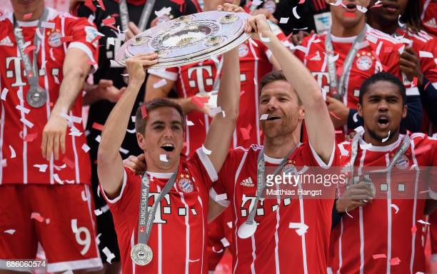 Philipp Lahm and Xabi Alonso of Bayern Muenchen lift the Championship trophy in celebration of the 67th German Championship title following the...