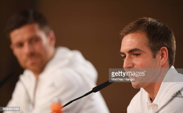 Philipp Lahm and Xabi Alonso of Bayern Muenchen talk during a press conference at Estadio Santiago Bernabeu on April 17 2017 in Madrid Spain