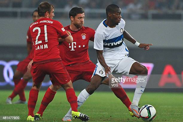 Philipp Lahm and Xabi Alonso of FC Bayern Muenchen and Geoffrey Kondogbia of Inter Milan compete for the ball during the international friendly match...