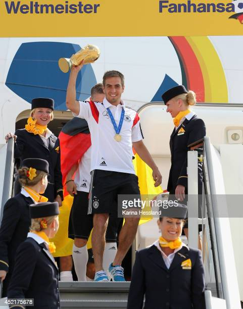 Philipp Lahm holds up the World Cup as the German national team return after winning the 2014 World Cup at Berlin Tegel Airport on July 15 2014 in...
