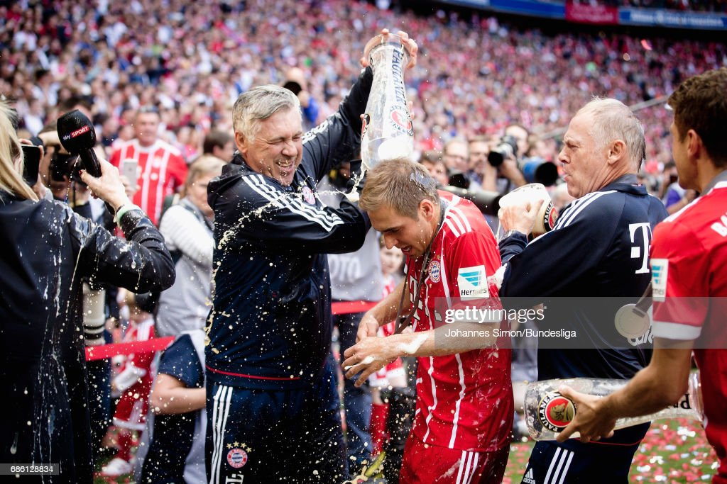 Philipp Lahm of Bayern (C) is showered by beer by head coach Carlo Ancelotti (L) after the awarding ceremony in celebration of the 67th German Championship title following the Bundesliga match between Bayern Muenchen and SC Freiburg at Allianz Arena on May 20, 2017 in Munich, Germany.