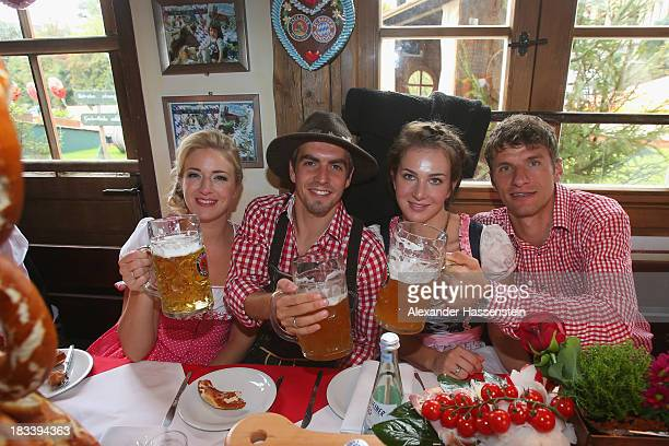 Philipp Lahm of Bayern Muenchen attends with his wife Claudia Lahm and Thomas Mueller with his wife Lisa Mueller the Oktoberfest 2013 beer festival...