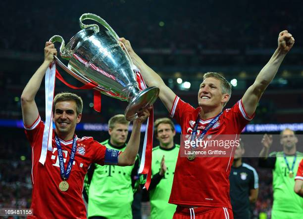 Philipp Lahm of Bayern Muenchen holds the trophy as he celebrates with teammate Bastian Schweinsteiger after winning the UEFA Champions League final...