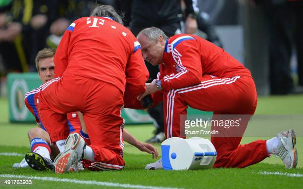 Philipp Lahm of Bayern Muenchen is treated by team doctor HansWilhelm MuellerWohlfahrt during the DFB Cup Final match between Borussia Dortmund and...