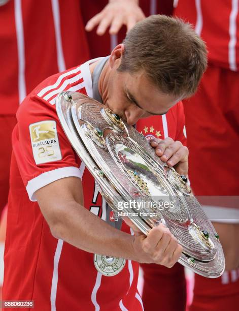 Philipp Lahm of Bayern Muenchen kisses the Championship trophy in celebration of the 67th German Championship title following the Bundesliga match...